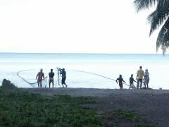Local fishermen pulling in their net off the beach