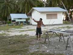 Young Ahe man preparing to throw spear