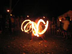 Fire dancer expertly paints the night with his fiery torches