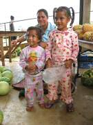 Adorable children helping Mom sell mangos and pineapples